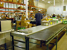 Shipping Station: Workers sort bin-stored product and release to the conveyor system so it can be put away.