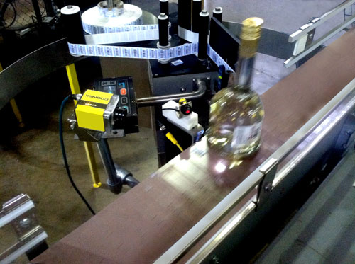 Conveyor labeling and barcode reader system for liquor distribution