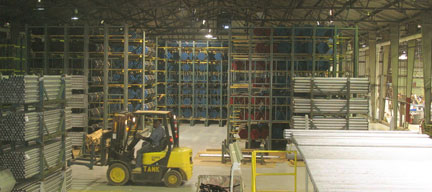 Workers pick and store PVC-coated pipe in a complex cantilever rack system