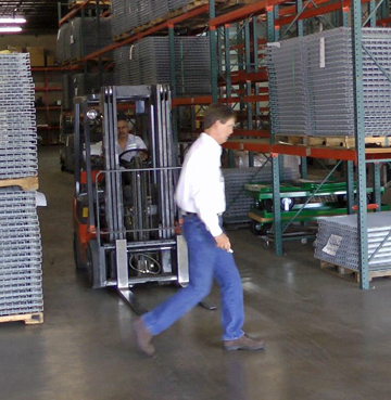 man walking in a forklift aisle