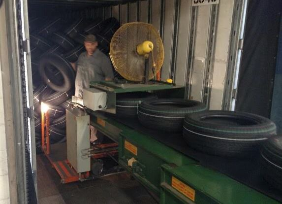 loading tires into a truck trailer with extendable conveyors