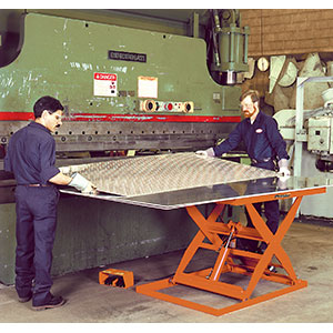 workers with sheet metal load on lift table