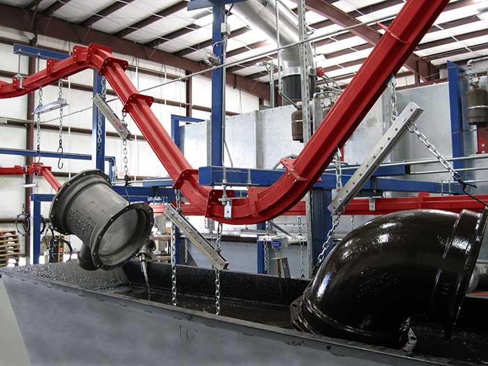Overhead conveyor moving heavy parts through a dip line