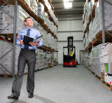 manager in a warehouse forklift area between rack aisles