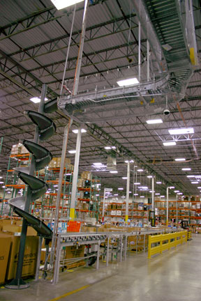 Very tall gravity chute interfaces with overhead roller conveyor system
